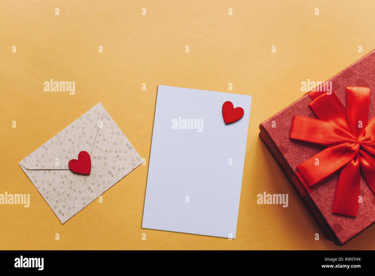 Blank sheet with red heart for text or write. Near an envelope with a heart to send and a box with a gift. Concept for Valentine's Day or Women's Day or Mother's Day. - Stock Image