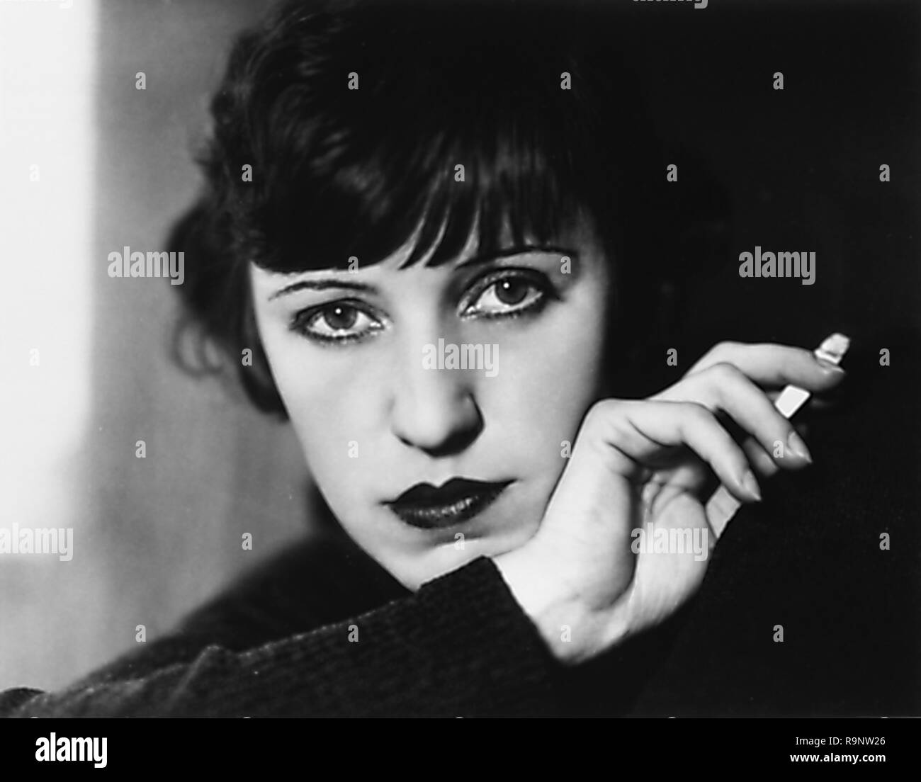 Black and white, headshot, portrait photograph, of Austrian-American actress, singer, and diseuse Lotte Lenya, facing the camera, with a neutral expression on her face, leaning her chin on her wrist, and holding a lit cigarette in her hand, photographed in Berlin, Germany, circa 1928, by the German-American portrait photographer Lotte Jacobi (1896-1990), 1928. () - Stock Image