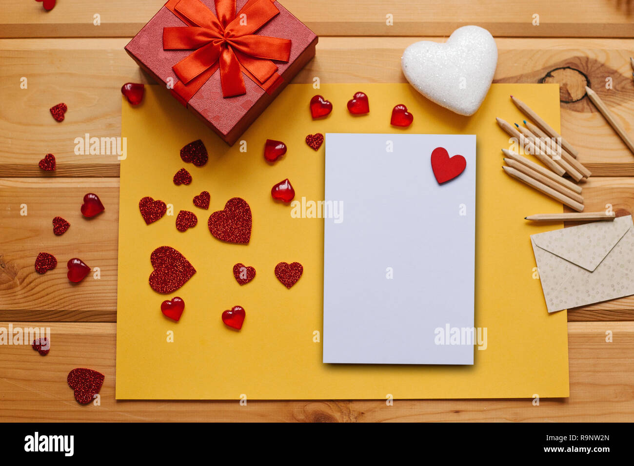 Blank sheet with red heart for text or write. Near an envelope to send and a box with a gift and many different hearts. Concept for Valentine's Day or Women's Day or Mother's Day. - Stock Image