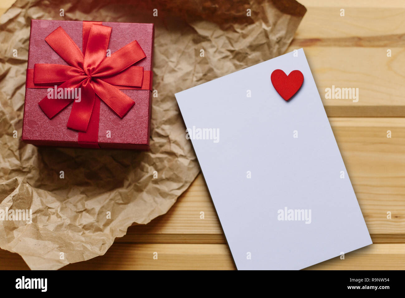 Red box with a gift and next to a white blank sheet for text with a heart on a wooden surface. Festive concept for Valentine's Day or Women's Day or Mother's Day. Stock Photo