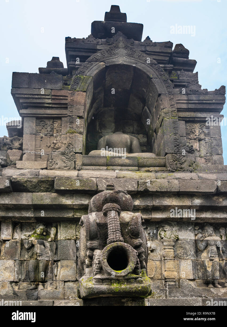 carved stormwater spout below a headless sitting Buddha statue in a niche at 9th century Borobudur Mahayana Buddhist temple, Central Java, Indonesia - Stock Image