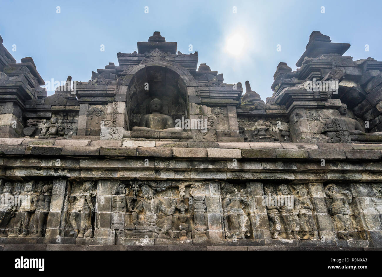 bas-relief panels with narratives of Buddhist mythology and life in Java of the period below niches with sitting Buddha statues on the terraces of 9th - Stock Image