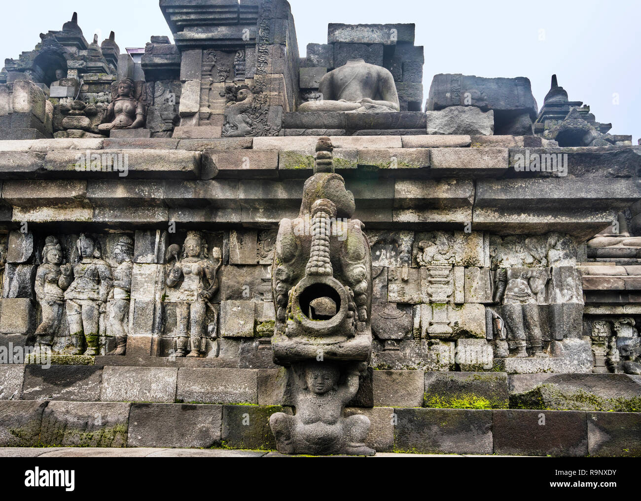 carved stormwater spout and bas-reliefs on a balustrade at 9th century Borobudur Mahayana Buddhist temple, Central Java, Indonesia - Stock Image