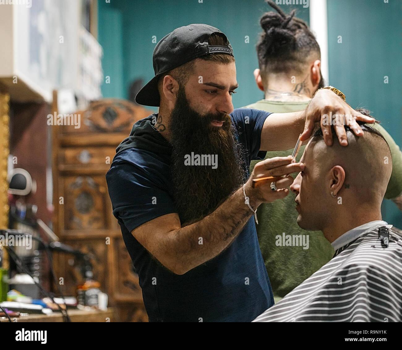 Brisbane, Australia-October 02,2018: Hipster hairdresser serves his client in an Australian barber shop. - Stock Image