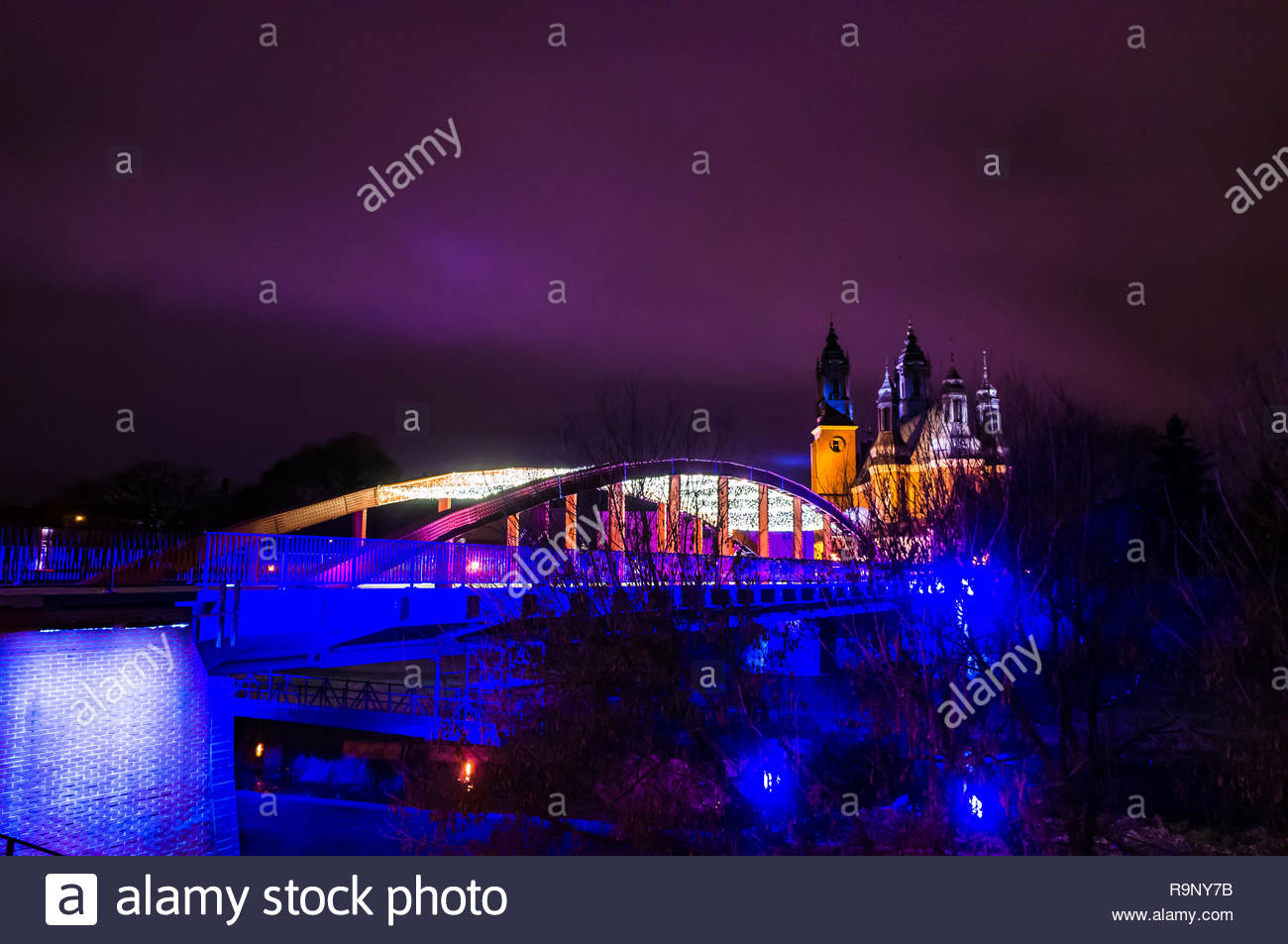 Poznan, Poland - December 26, 2018: Jordan bridge with Christmas lights over the Warta river by night. Cathedral on the Ostrow Tumski in the background.  Stock Photo