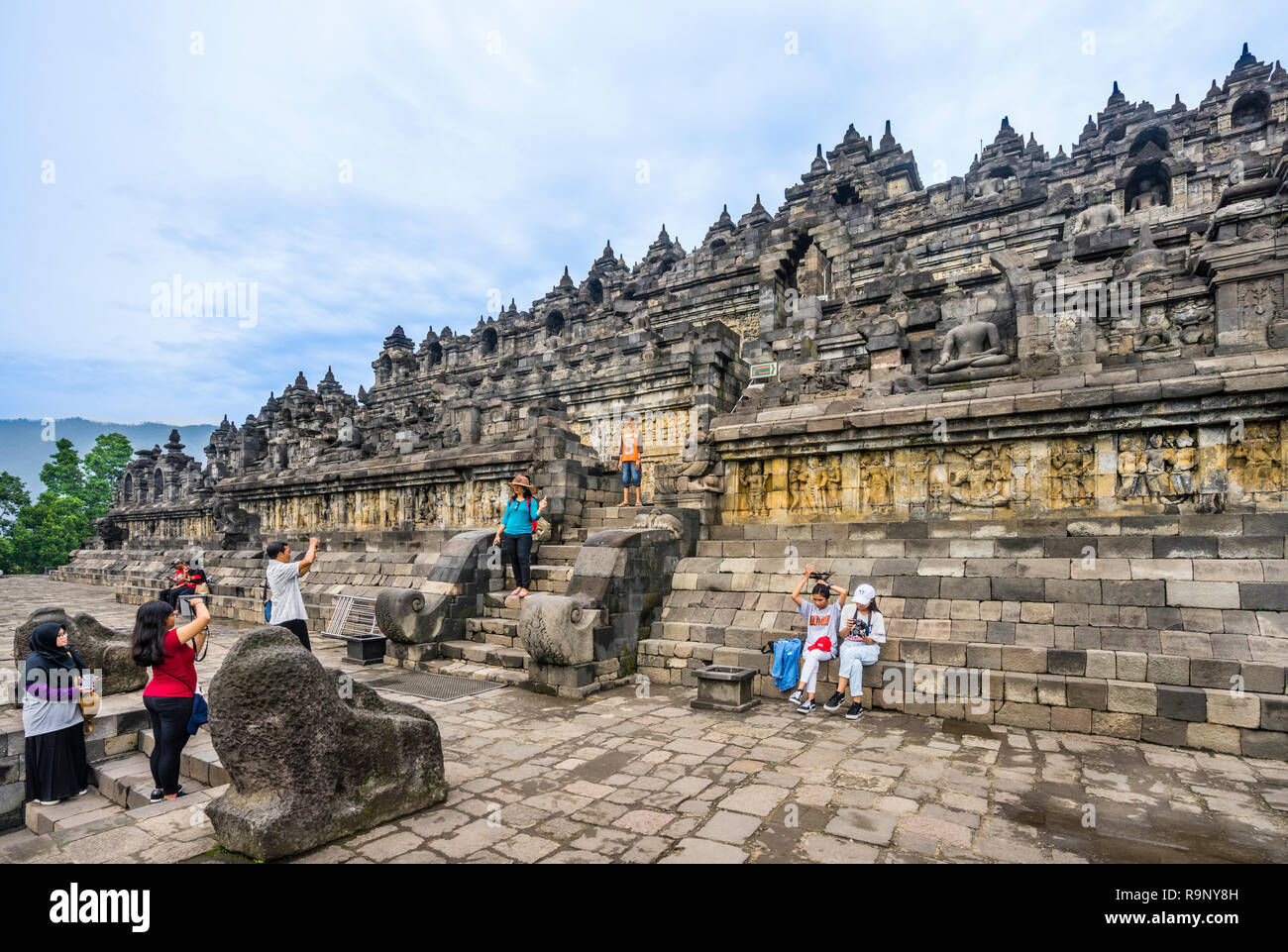 visitors at the ascent to the mandala step pyramid of 9th century Borobudur Buddhist temple, Central Java, Indonesia - Stock Image