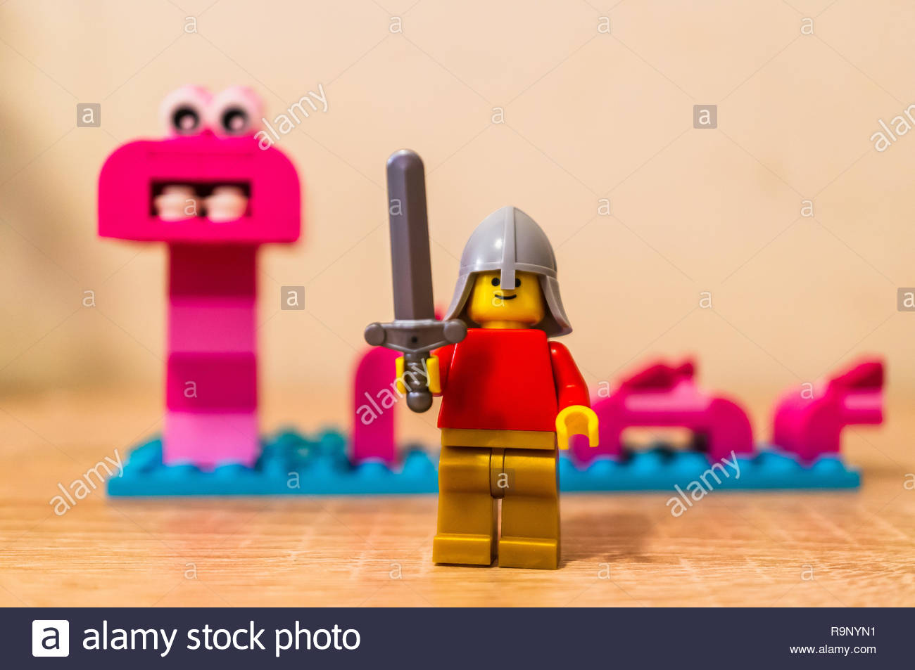 Poznan, Poland - December 26, 2018: Lego warrior holding a sword with monster in soft focus background. - Stock Image