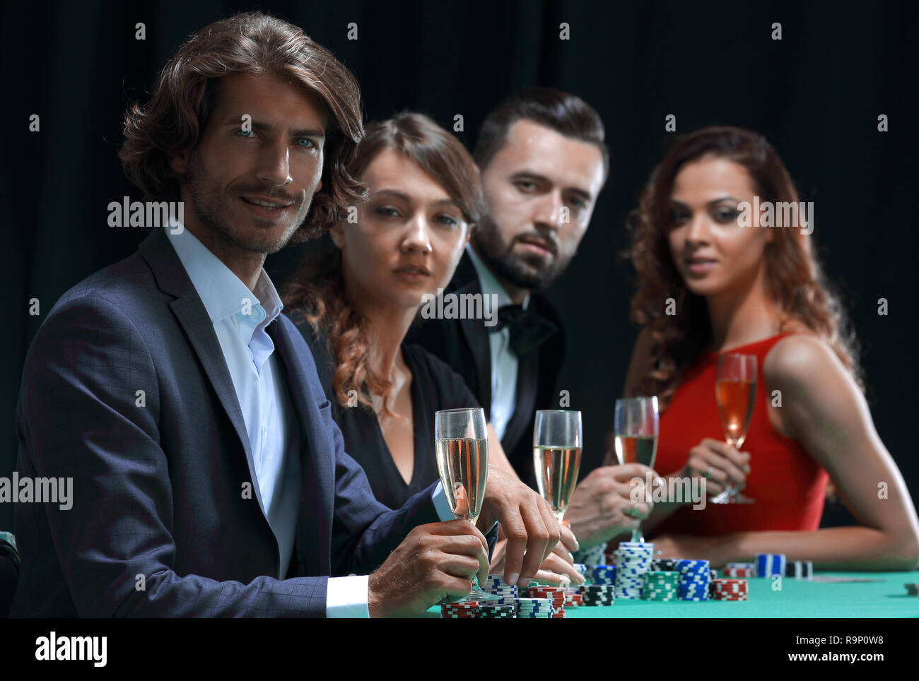 Poker players drink champagne on a black background - Stock Image