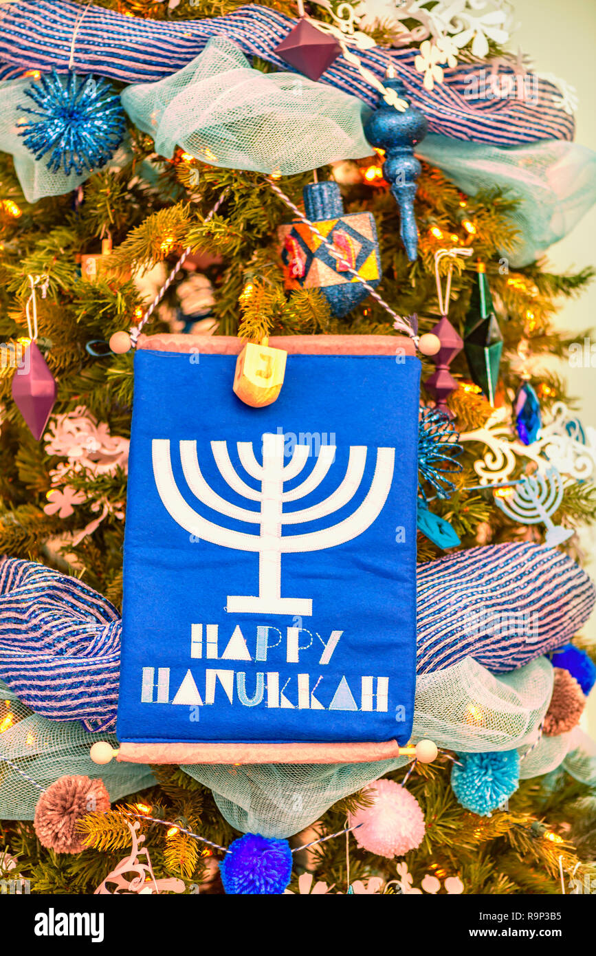 Christmas tree is beautifully decorated with colorful toys, garlands, stars, a candlestick and a flag with the inscription Happy Hanukkah. Stock Photo