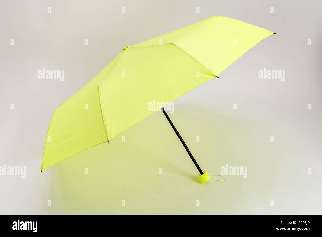 a white background and a yellow umbrella - Stock Image
