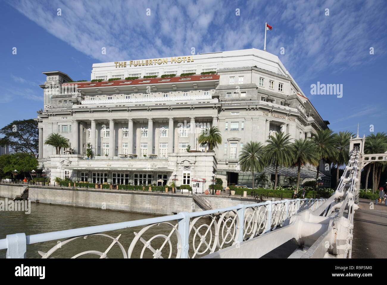 Cavenagh Bridge near to Fullerton Hotel. This is a 5-stars neoclassical hotel located beside the Singapore River, Singapore. - Stock Image