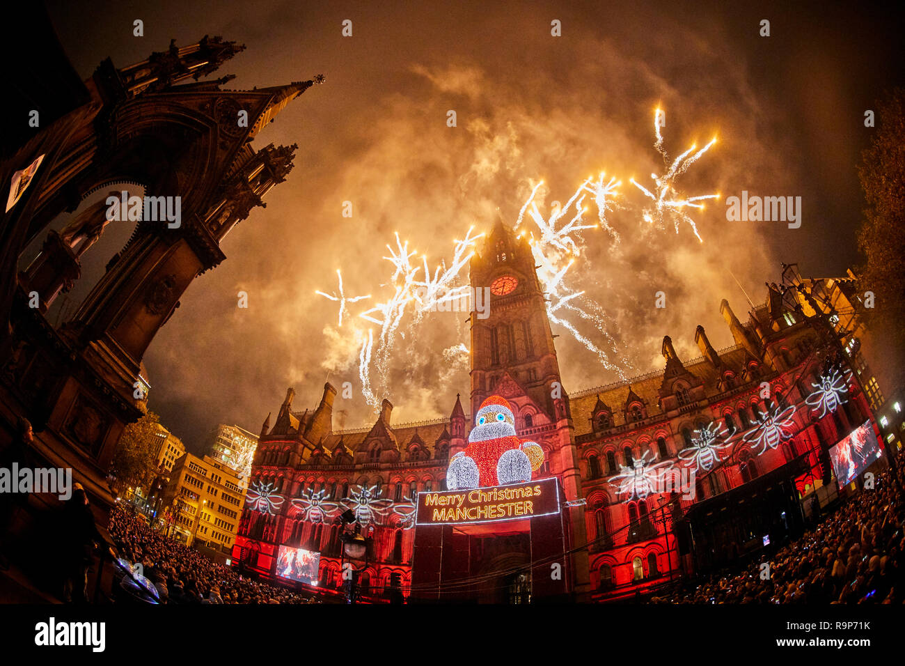 Manchester 2018 Christmas light switch Albert Square  Fireworks explode in the sky above the landmark town hall building with zippy the santa r Stock Photo