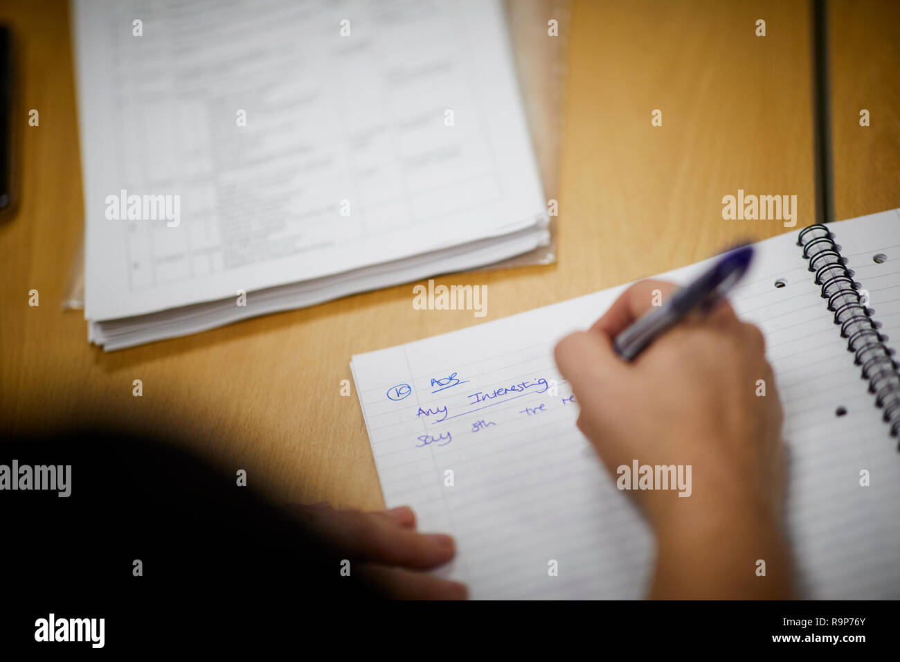 Writing notes in a school note book line paper homework at a desk - Stock Image