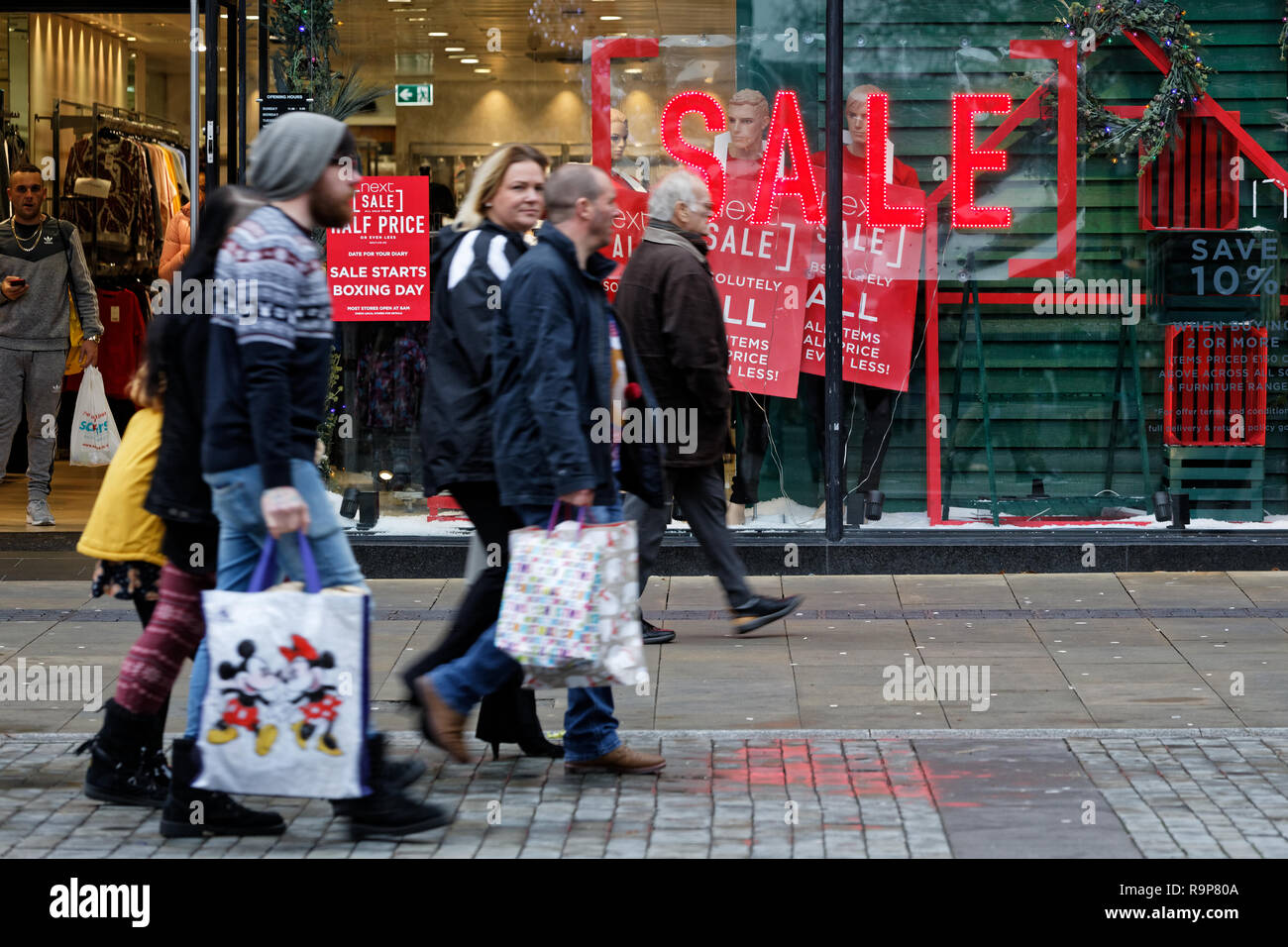 Last minute Christmas shoppers walk past a 'Sale' sign outside Next store in Oxford Street, Swansea, Wales, UK. Monday 24 December 2018 - Stock Image