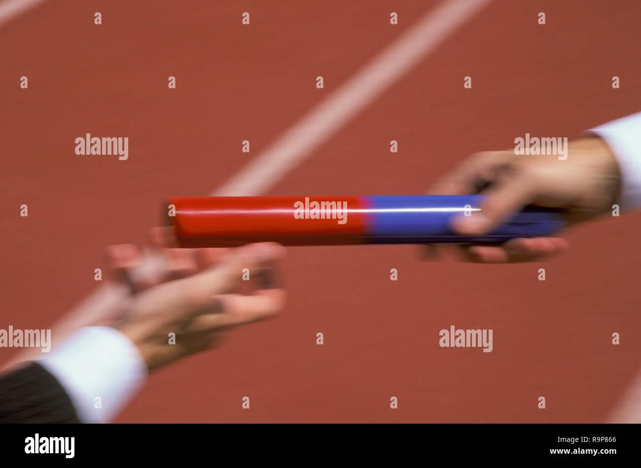 Businessmen passing the baton on running track, USA - Stock Image