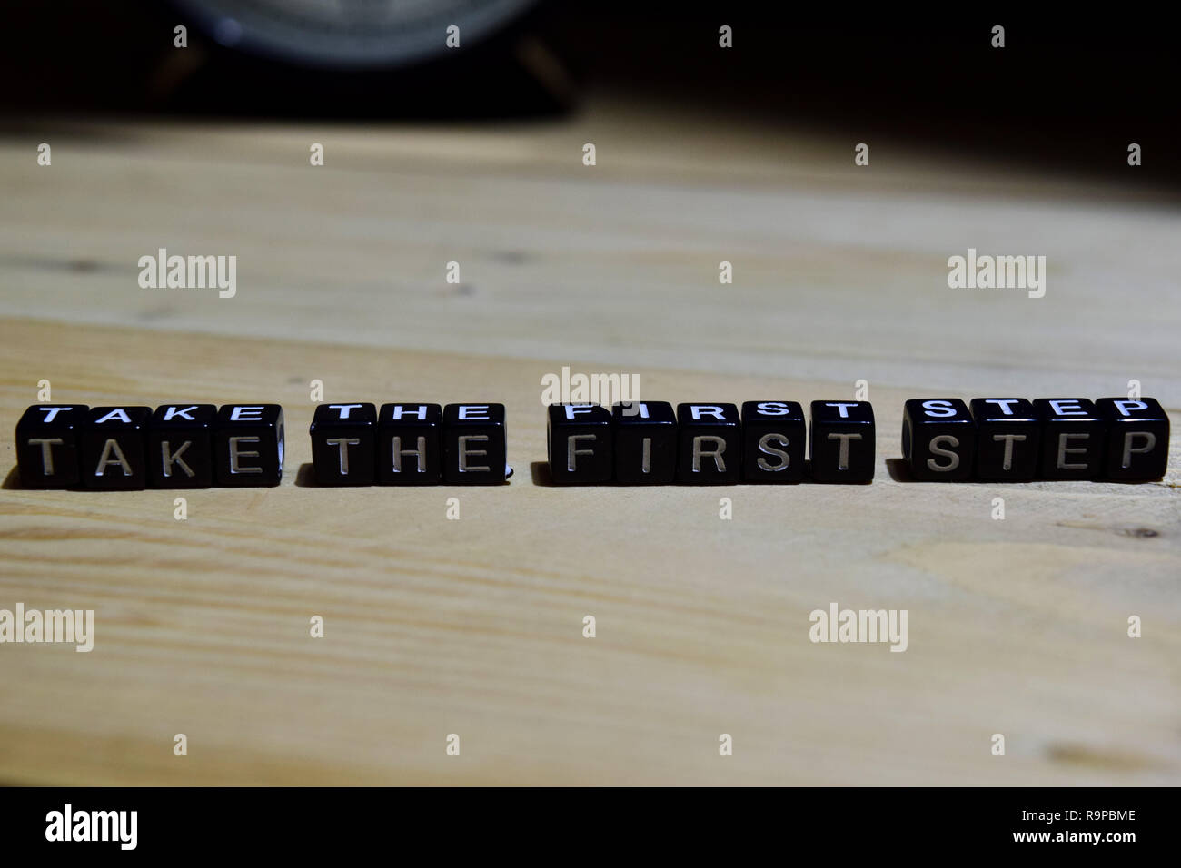 Take the first step written on wooden blocks. Education and business concept on wooden background - Stock Image