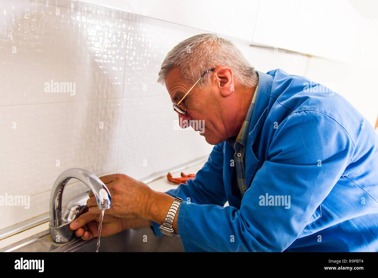 Repairman in blue working suit repair kitchen faucet Stock Photo