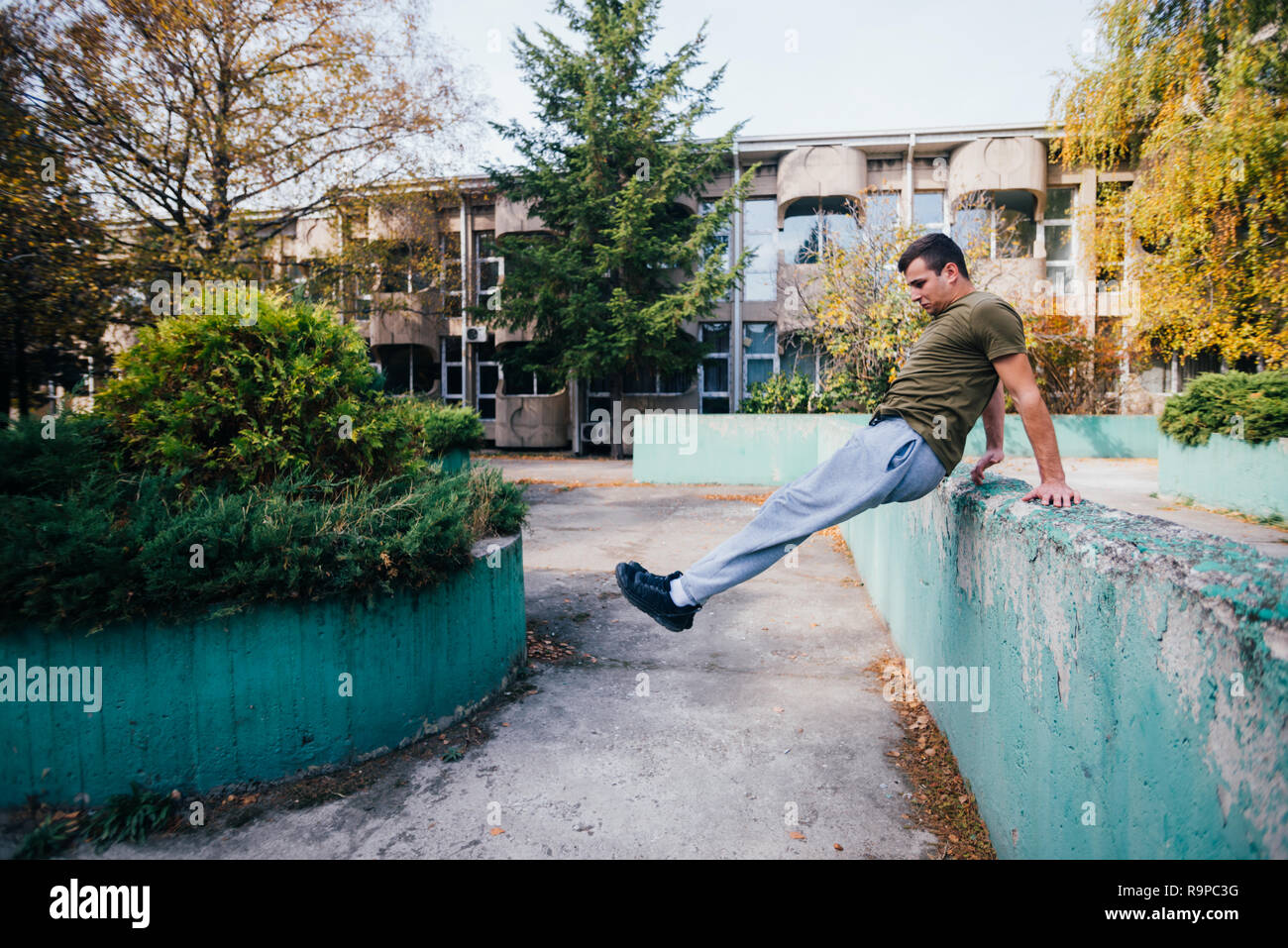 Young parkour guy jumping over a concrete wall and landing on another concrete wall while doing tricks in the air. Stock Photo