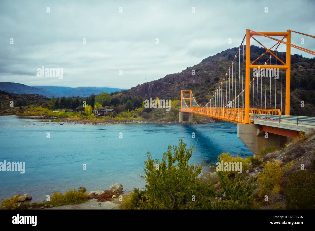 Red suspension bridge over the water runoff of General Carrera Lake, near Lake Bertrand, Puerto Tranquilo, Chile Chico, Aysen, Chile - Stock Image