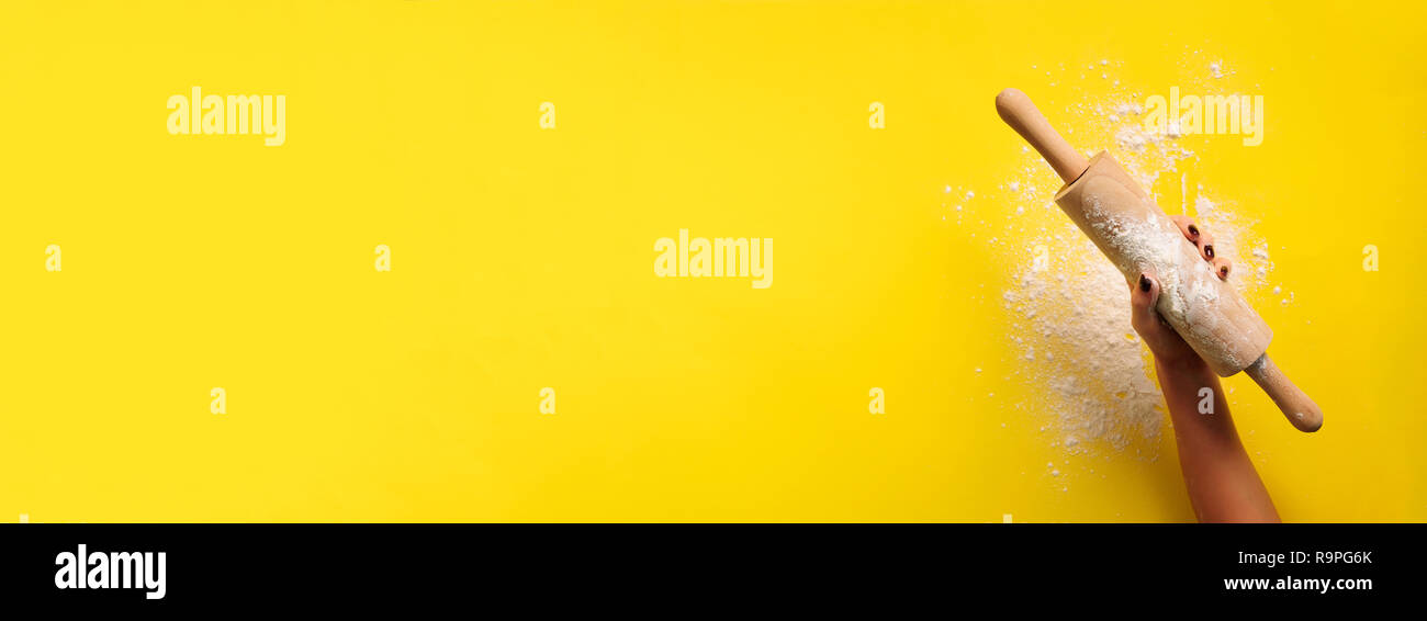 Girl hands keep rolling pin with flour on yellow background. Bake menu, recipe, homemade pastry concept. Top view. Banner with copy space for your tex Stock Photo