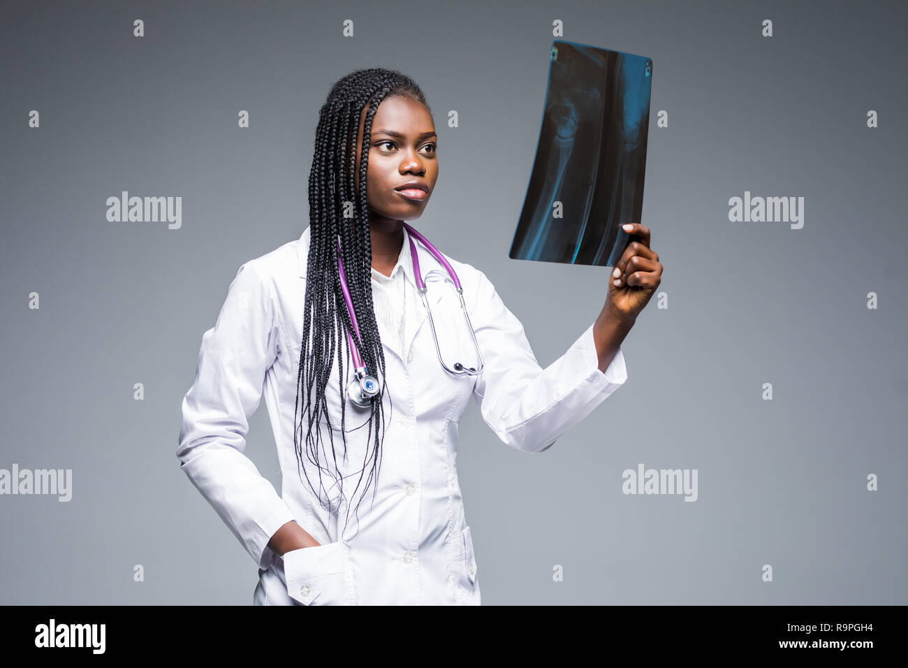 Beautiful african doctor woman with X-ray of lungs, fluorography, roentgen isolated on gray background. - Stock Image
