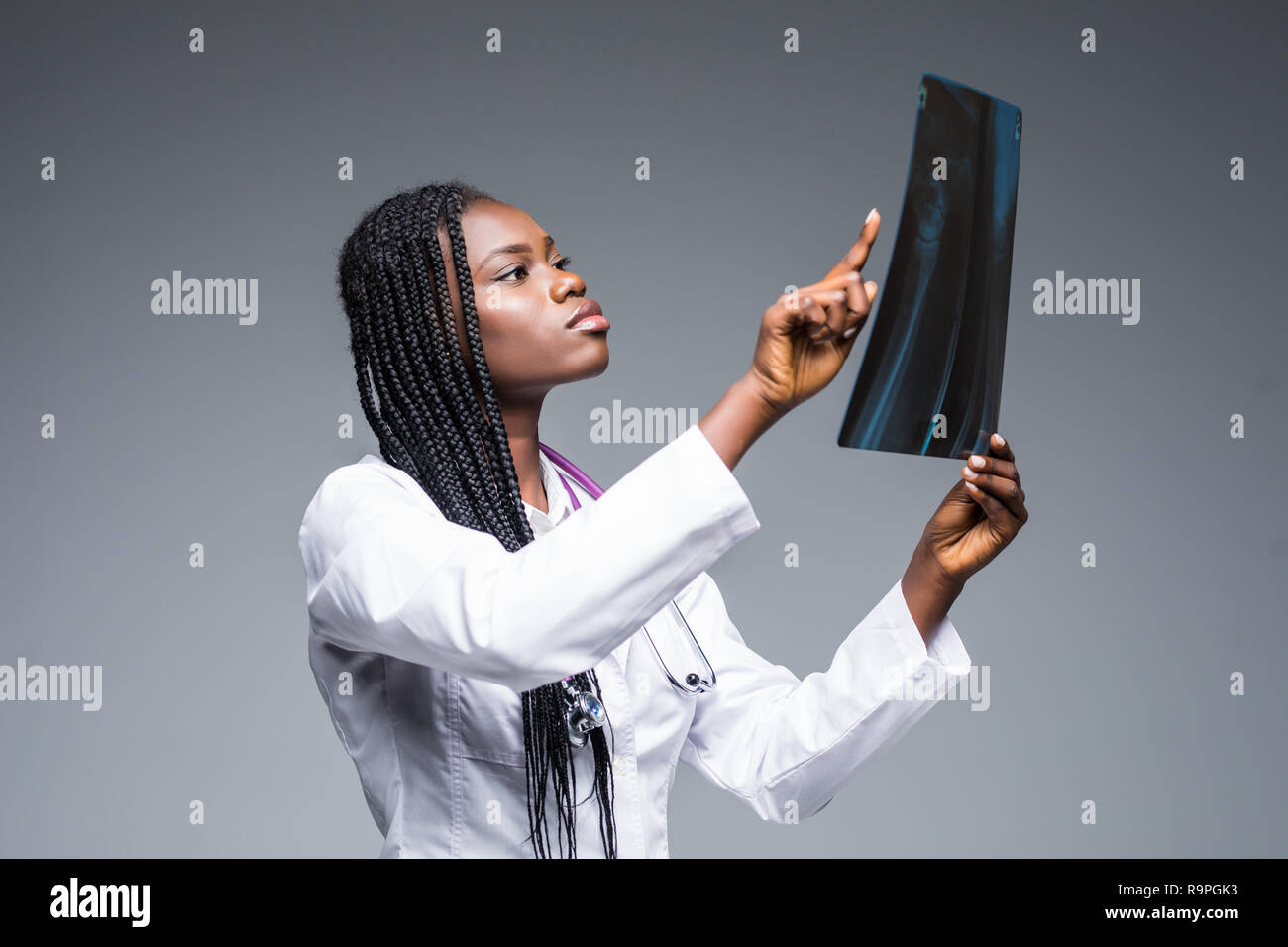 Closeup portrait of doctor woman healthcare personnel with white labcoat, looking at full body x-ray radiographic image, ct scan, mri, isolated gray b - Stock Image
