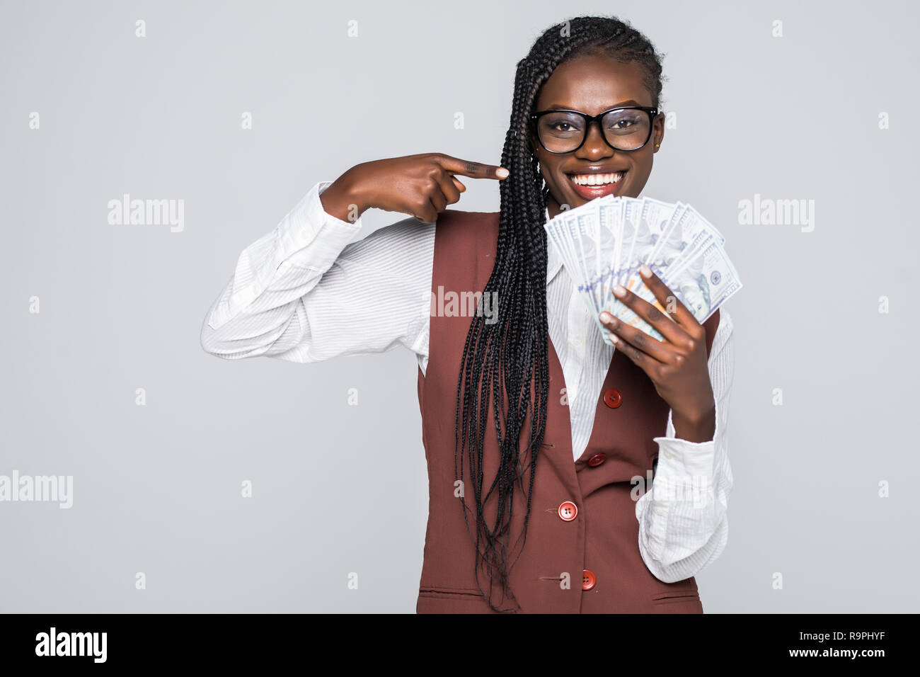 Portrait of excited woman with afro hairstyle pointing finger on fan of money dollar bills isolated over gray background - Stock Image
