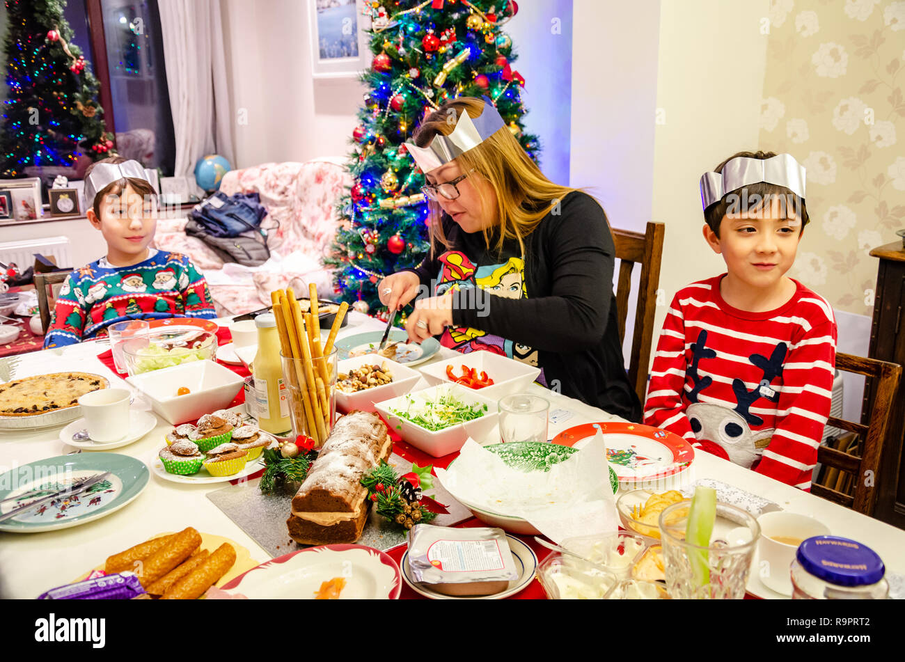 A family sit at a dining table laid out with salad for a Christmas tea, - Stock Image