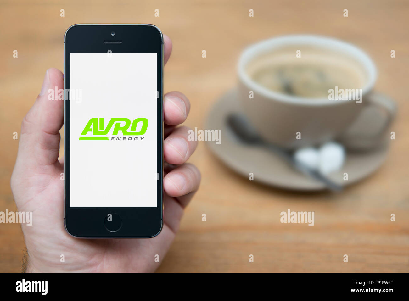 A man looks at his iPhone which displays the Avro Energy logo (Editorial use only). - Stock Image