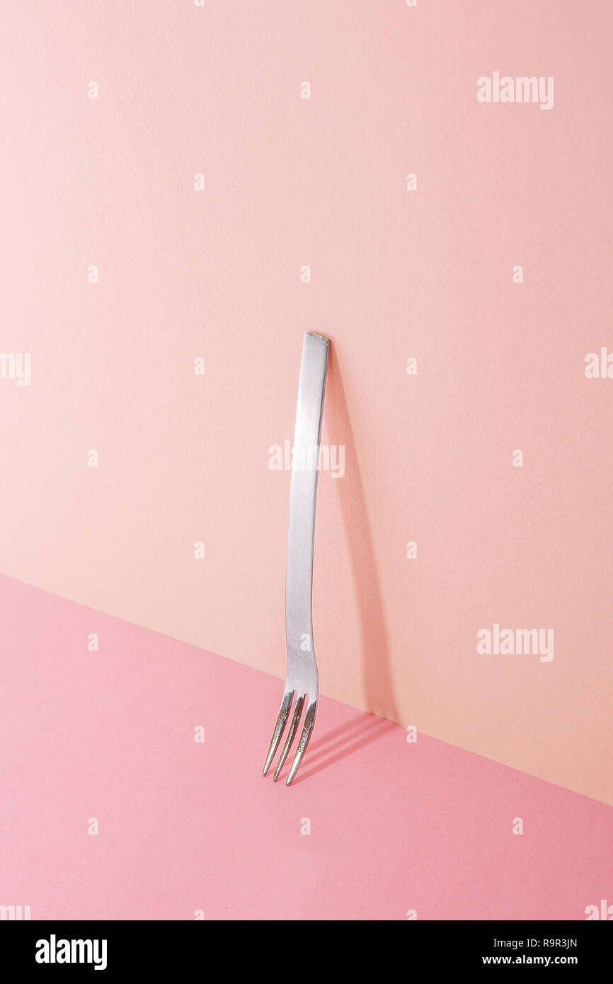 a fork. Pink Two Tone Background. - Stock Image