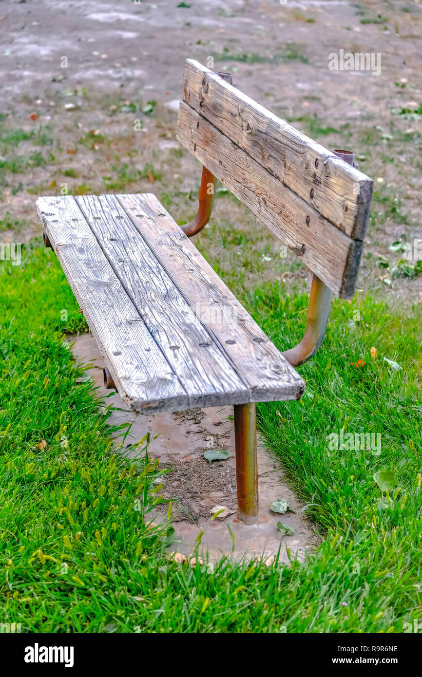 Wooden bench painted white on a grassy terrain Stock Photo