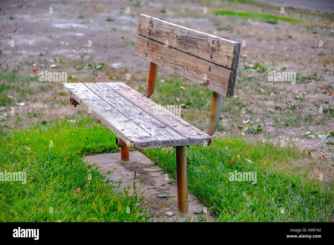 Old wooden bench on grassy terrain in Provo Utah Stock Photo