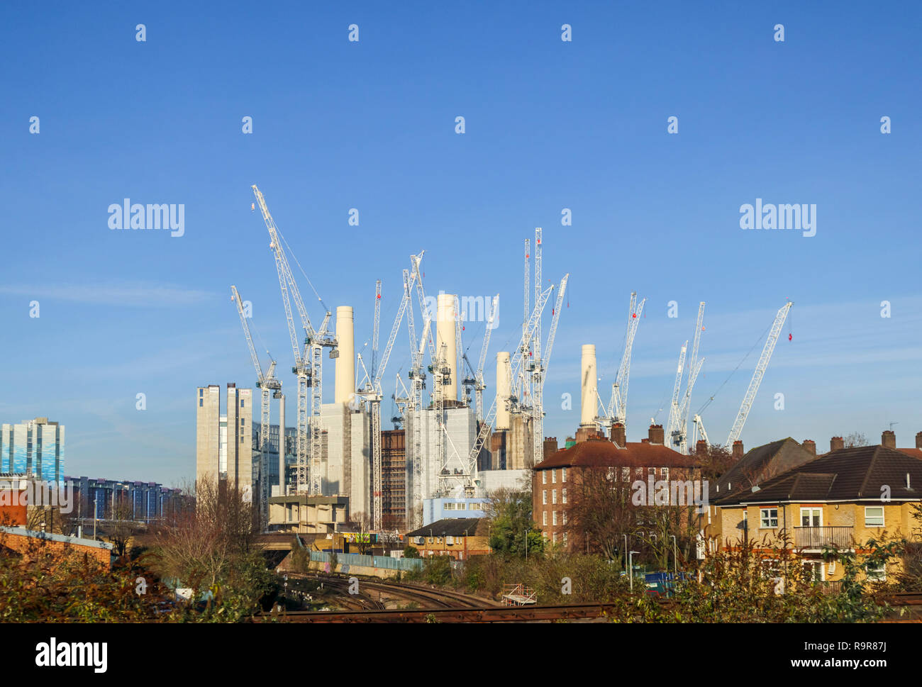 White tower cranes surround the iconic decommissioned Battersea Power Station being redeveloped for mixed uses and high class luxury apartments Stock Photo