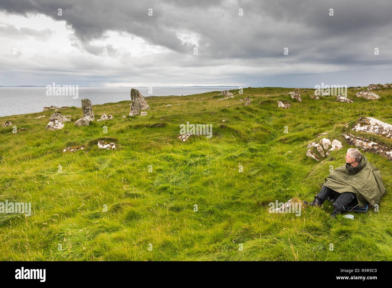 Person seeking protection against the rain, sitting on the grass. Fetlar, Shetland Islands. Stock Photo