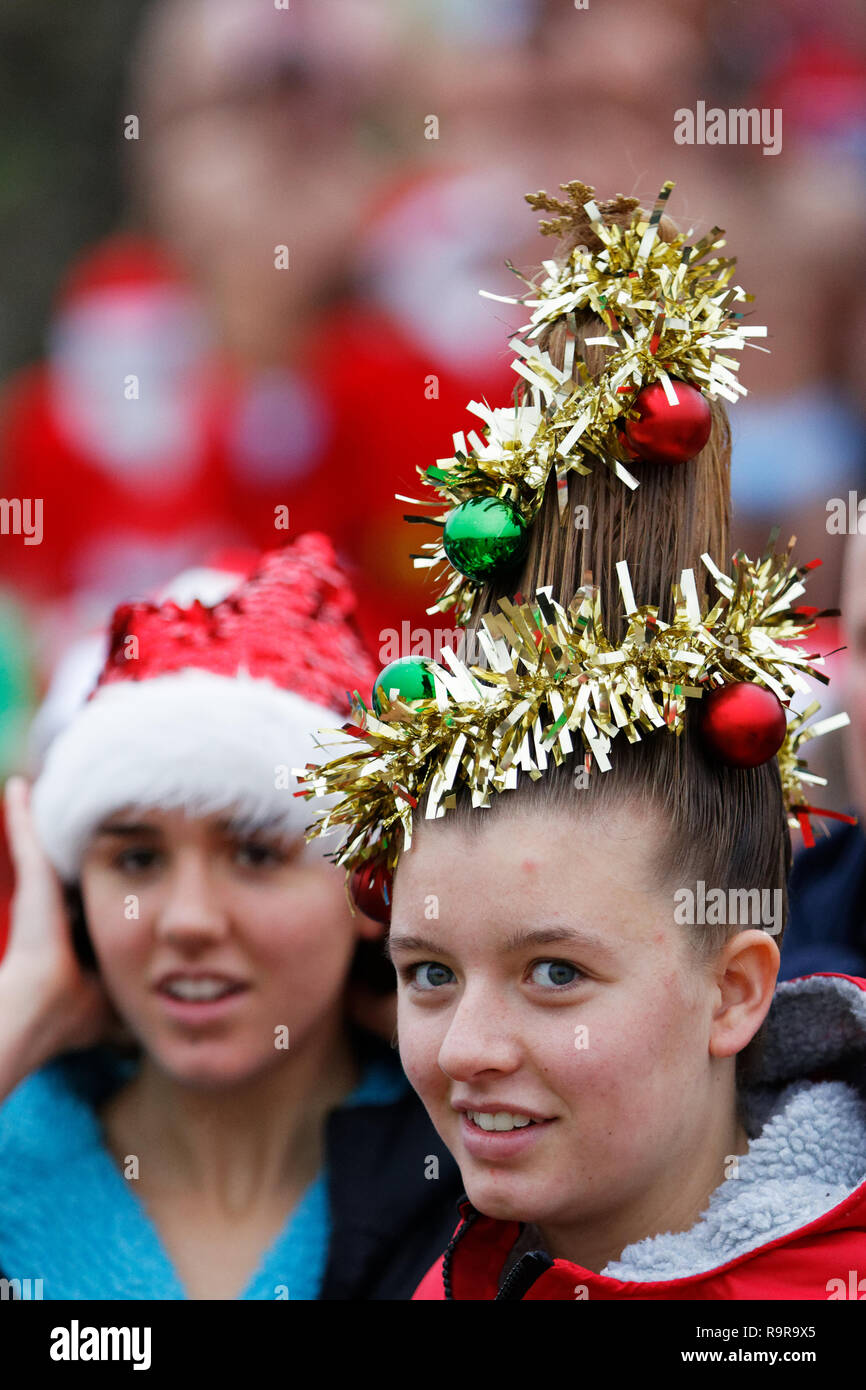 Pictured: A young woman with a Christmas Tree hairdo. Tuesday 25 December 2018 Re: Hundreds of people take part in this year's Porthcawl Christmas Swi - Stock Image