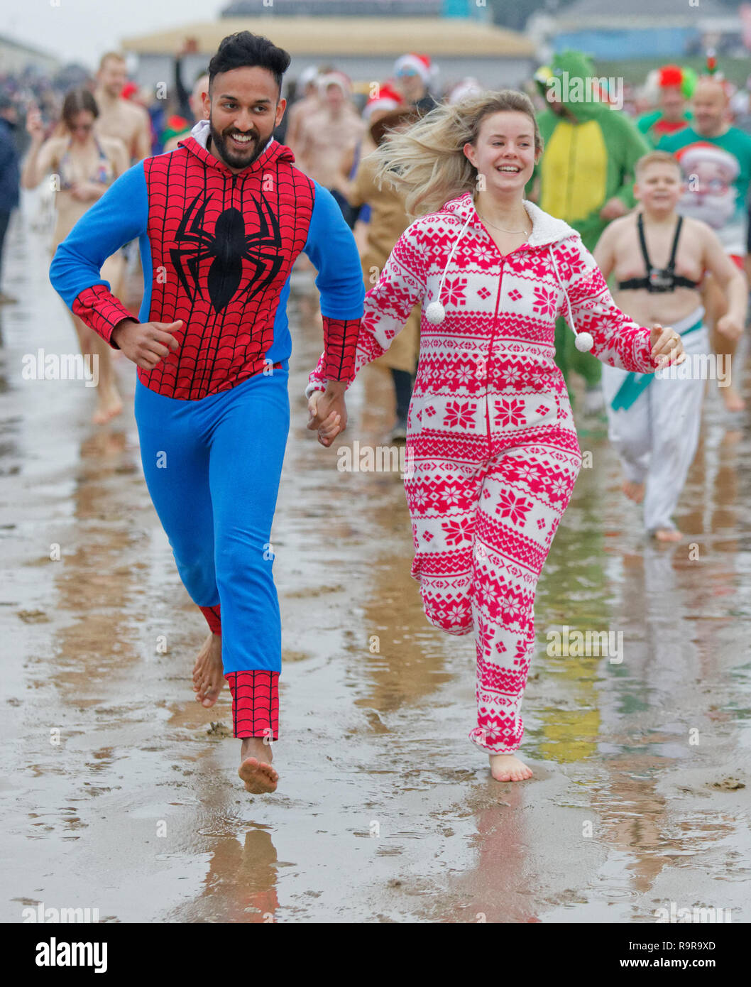 Pictured: A man dressed as Spiderman and a young woman in a festive onesie, run to the sea. Tuesday 25 December 2018 Re: Hundreds of people take part  Stock Photo