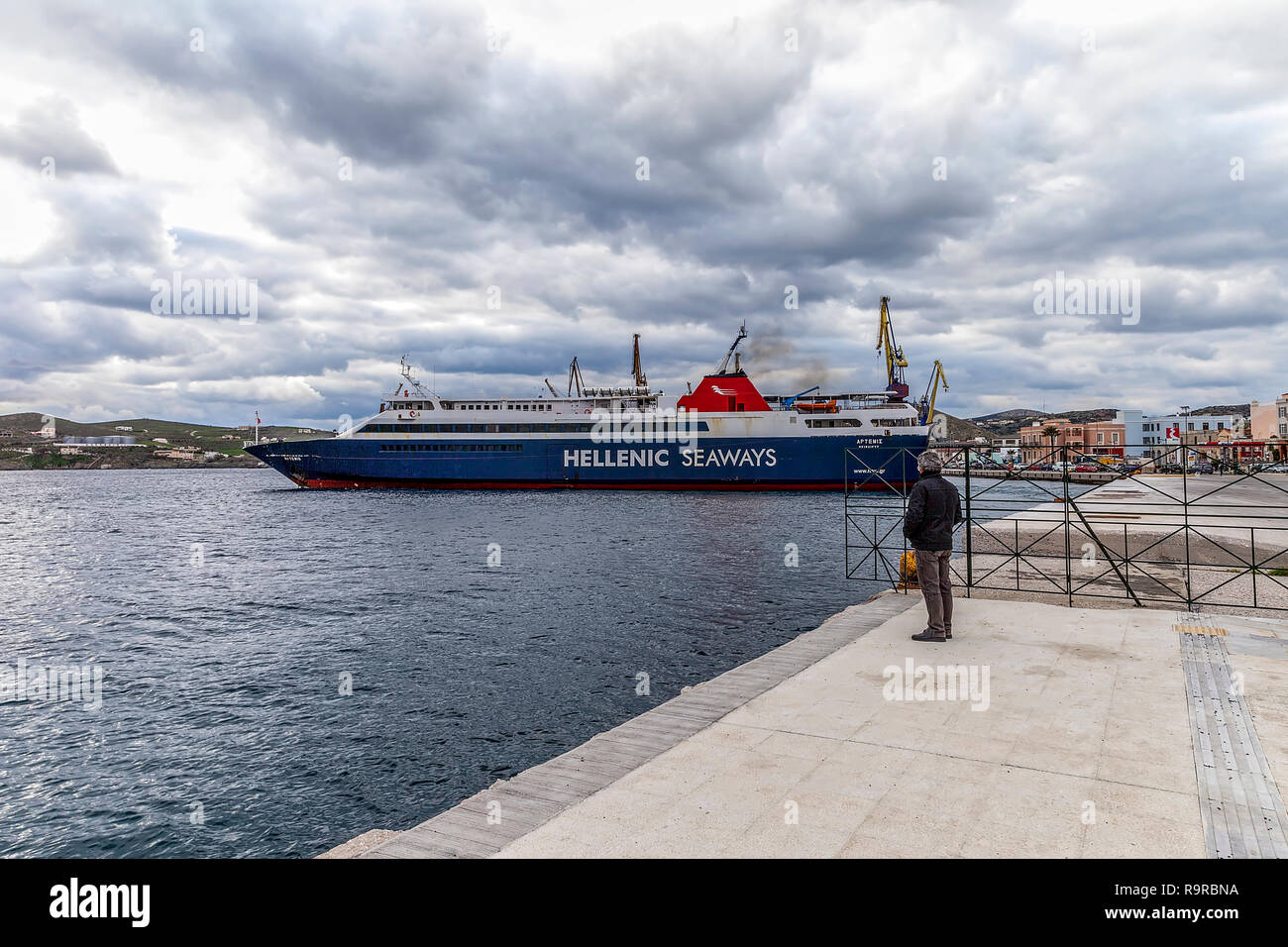 Ermoupolis: 27th December. Hellenic Seaways Ferry boat leaving Ermoupolis harbour. Man standing watching its deparchure. Ermoupolis, Syros, December 2 - Stock Image