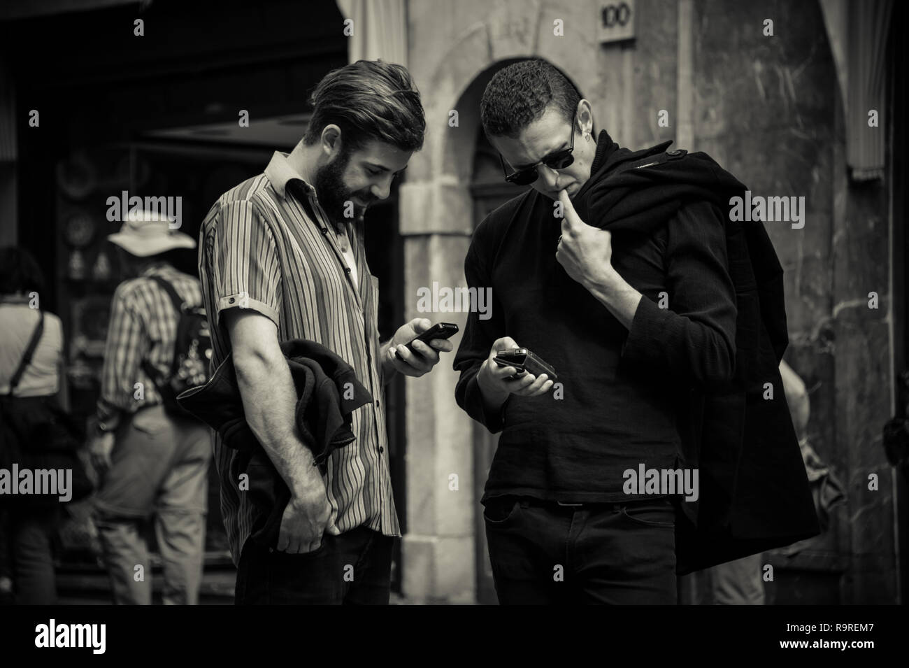 Two guys looking at mobile phones at street of Sicily, Italy - Stock Image