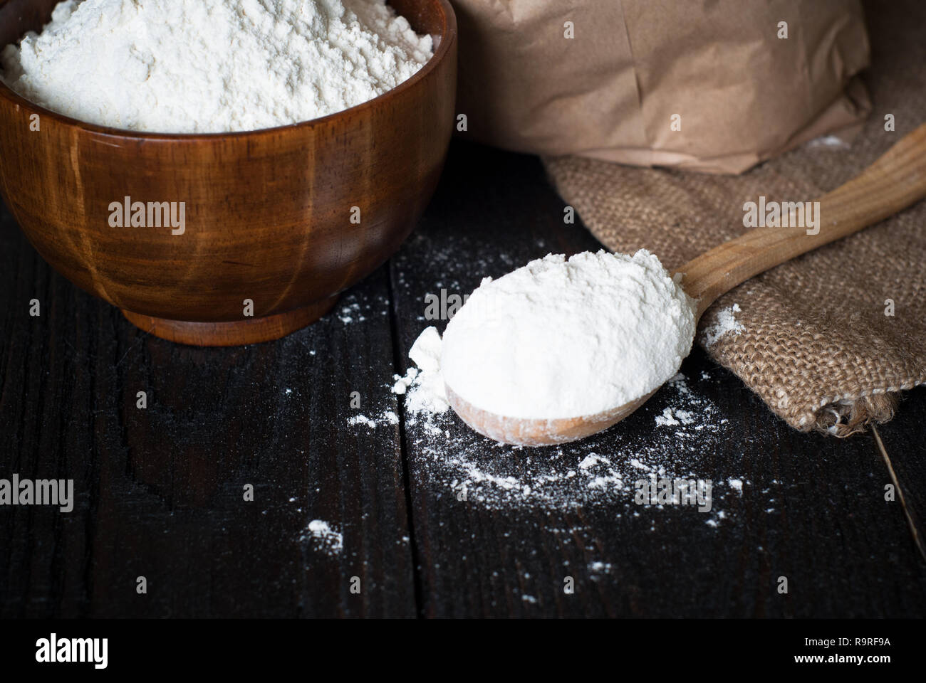 Flour in a wooden bowl, paper bag and spoon. Rustic Style, space for text. - Stock Image