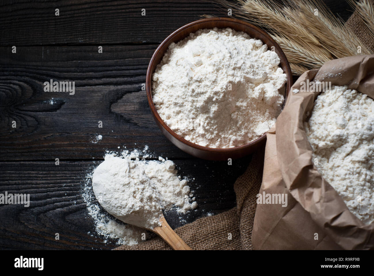 Flour in a wooden bowl, paper bag and spoon. Top view, space for text. - Stock Image