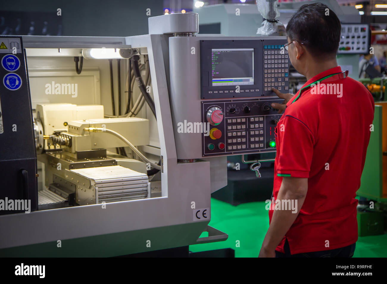 Worker input data for programing CNC machine - Stock Image