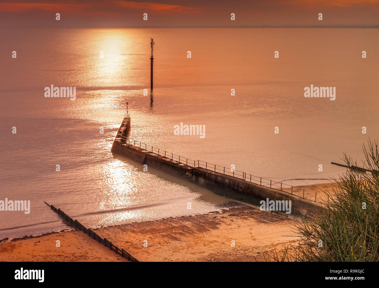 West cliff Ramsgate, uk beach and water breaker walkway late afternoon in winter as the sun is starting to set,making the sea shimmer and the light tu - Stock Image