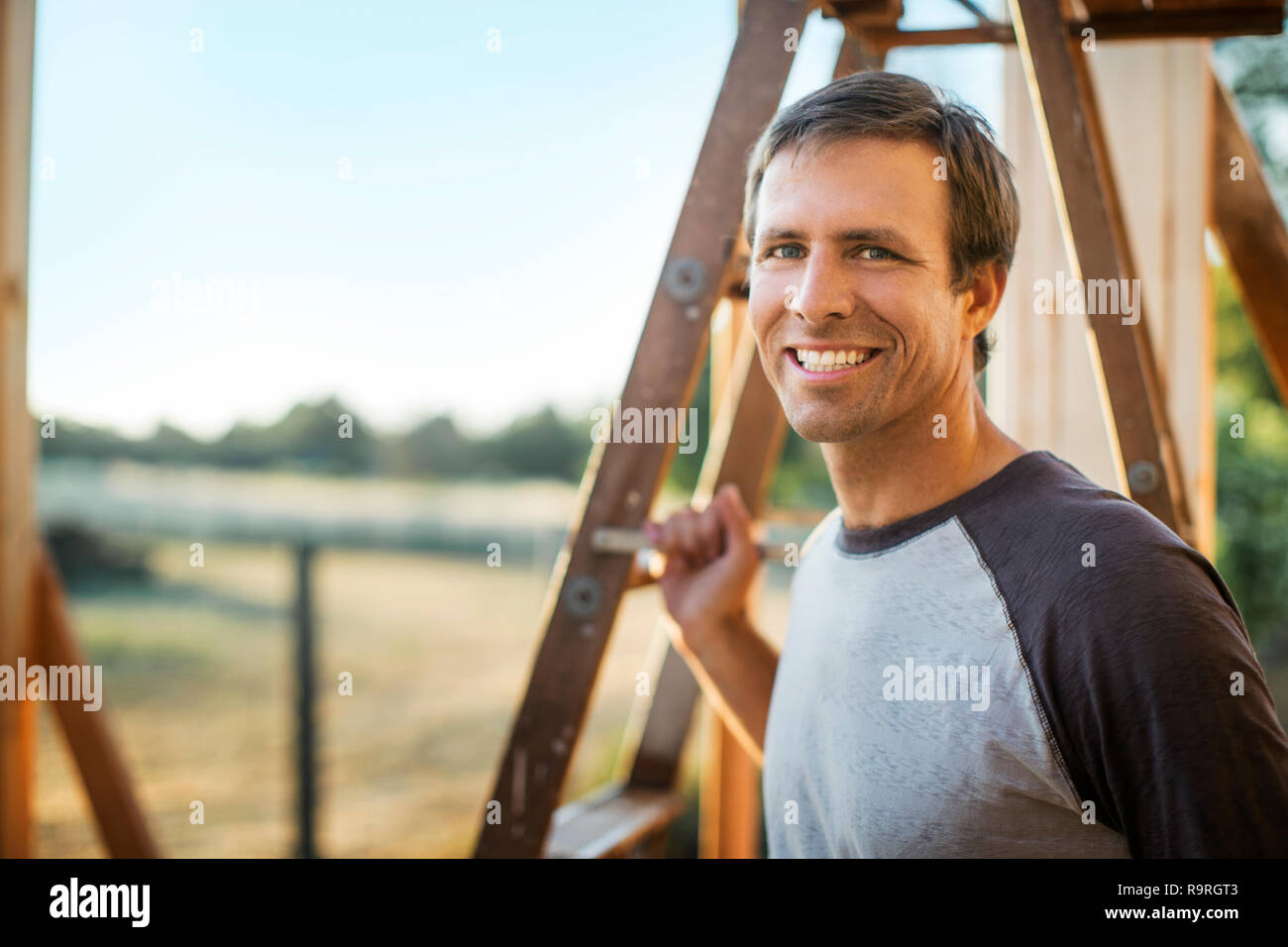 Smiling man stands next to a ladder in a house under construction. - Stock Image