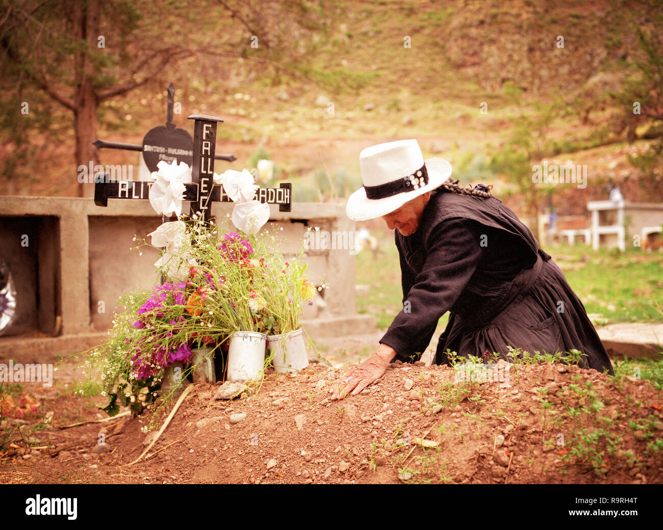 A mature woman weeps beside her beloveds grave. - Stock Image