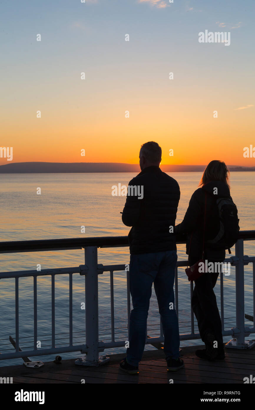 Bournemouth, Dorset, UK. 27th Dec, 2018. Beautiful sunset over Bournemouth beach at the end of a lovely sunny day, as visitors head to the pier and beach to watch the sun go down. Couple. Credit: Carolyn Jenkins/Alamy Live News Stock Photo