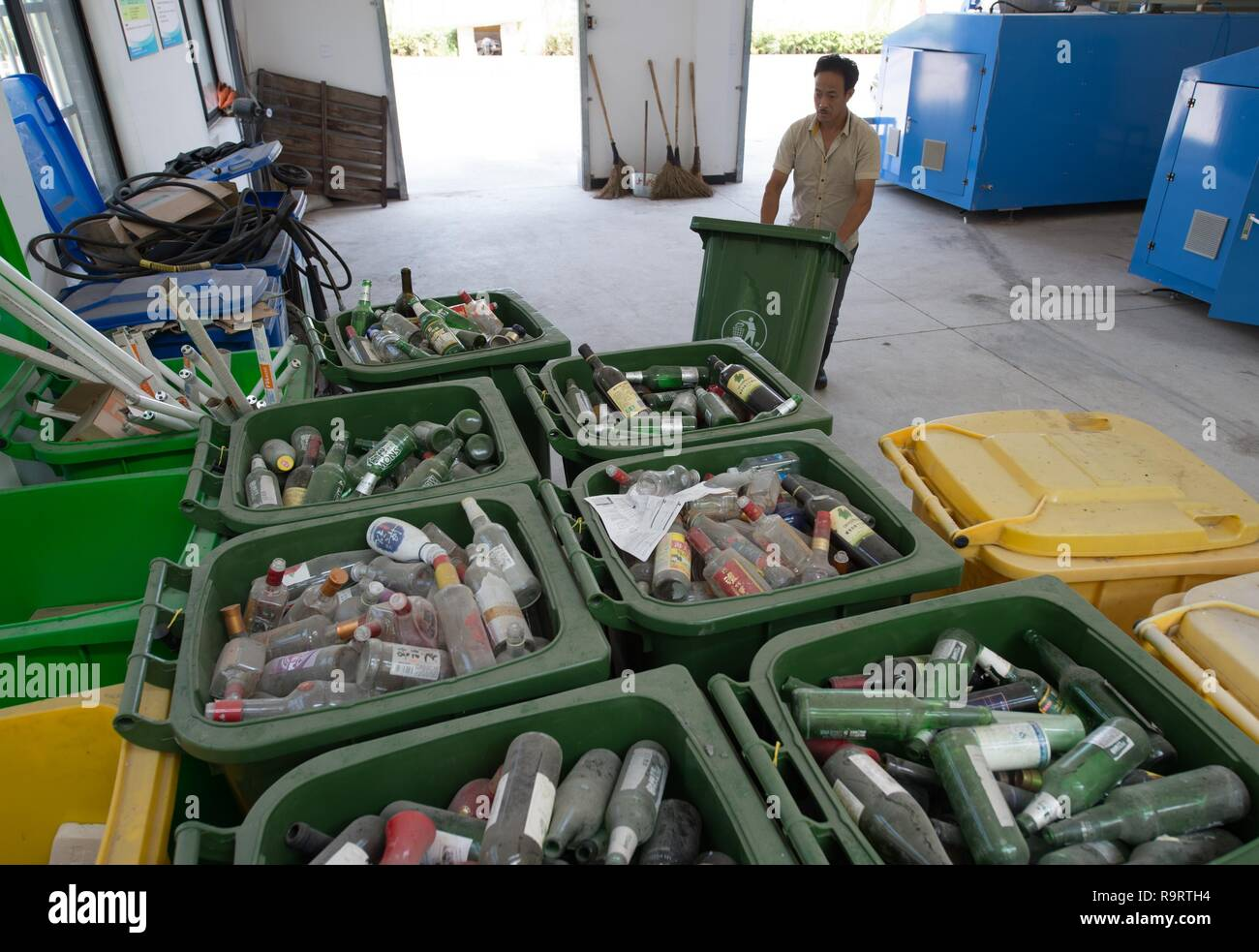 Beijing, China's Zhejiang Province. 3rd Aug, 2017. A staff member sorts and recycles glass products at Mulianwu Village in Anji County, east China's Zhejiang Province, Aug. 3, 2017. Since 2003, Zhejiang has implemented a project to overhaul the living environment in villages. At the end of last year, 97 percent of villages in the province had completed such overhauls. Credit: Weng Xingyang/Xinhua/Alamy Live News - Stock Image