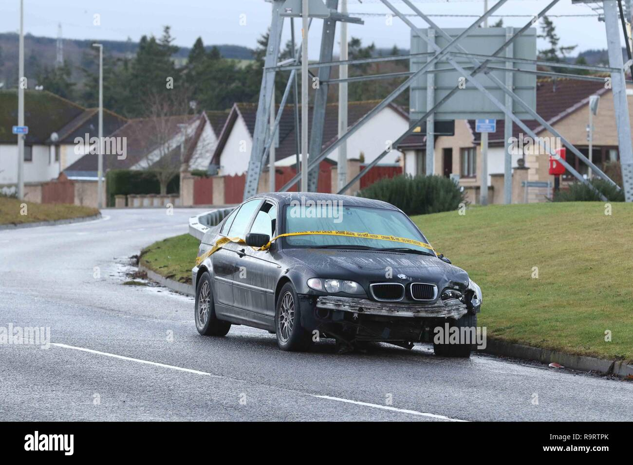 Inverness, Scotland, UK. 28 December 2018. Police in Inverness are trying to trace the driver of a black BMW that was involved in a single-vehicle collision over Christmas. The abandoned vehicle was reported to police on Boxing Day and was still in situ on Essich Road two days later with crime scene tape wrapped around it. There is substantial damage to the front of the vehicle and the nearside door mirror, and the driver's window is partially open. Picture Credit: Andrew Smith/Alamy Live News - Stock Image