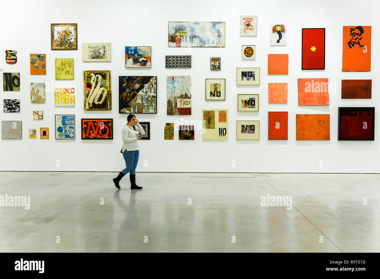 A woman seen walking front of art works of Boris Lurie Pop-art after the Holocaust exhibition. Boris Lurie (1924-2008) is an American artist of Jewish origin who was born in Leningrad (today St. Petersburg). In August 1941, the Germans began deporting the local Jewish population to the ghetto in Riga, where Boris Lurie spent his childhood. His Grandmother, mother, sister and beloved  were shot in a forest near Rumbuli in the Riga suburbs in December 1941. his work is closely related to this experience during the Holocaust. The motifs appearing in his works are photos from concentration camps,  Stock Photo