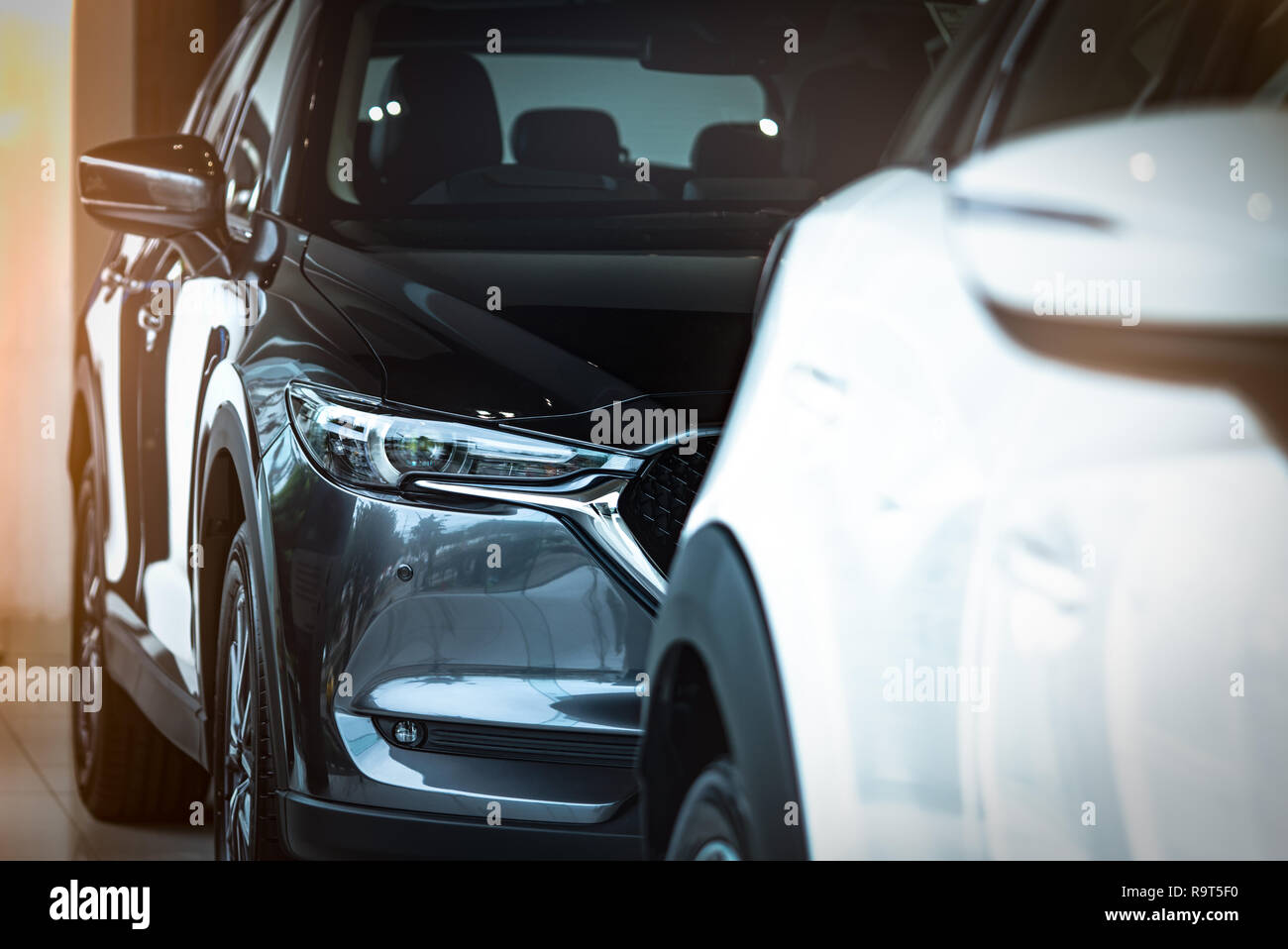 New luxury shiny SUV compact car parked in modern showroom. Car dealership office. Car retail shop. Electric car technology and business concept. Auto - Stock Image