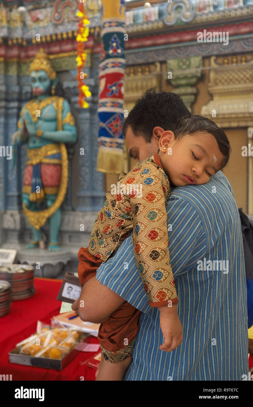 An ethnic Indian child sleeping on her father's shoulder in front of Sri Krishnan (Hindu) Temple, Waterloo St., Singapore, a Hanuman statue in the b/g - Stock Image